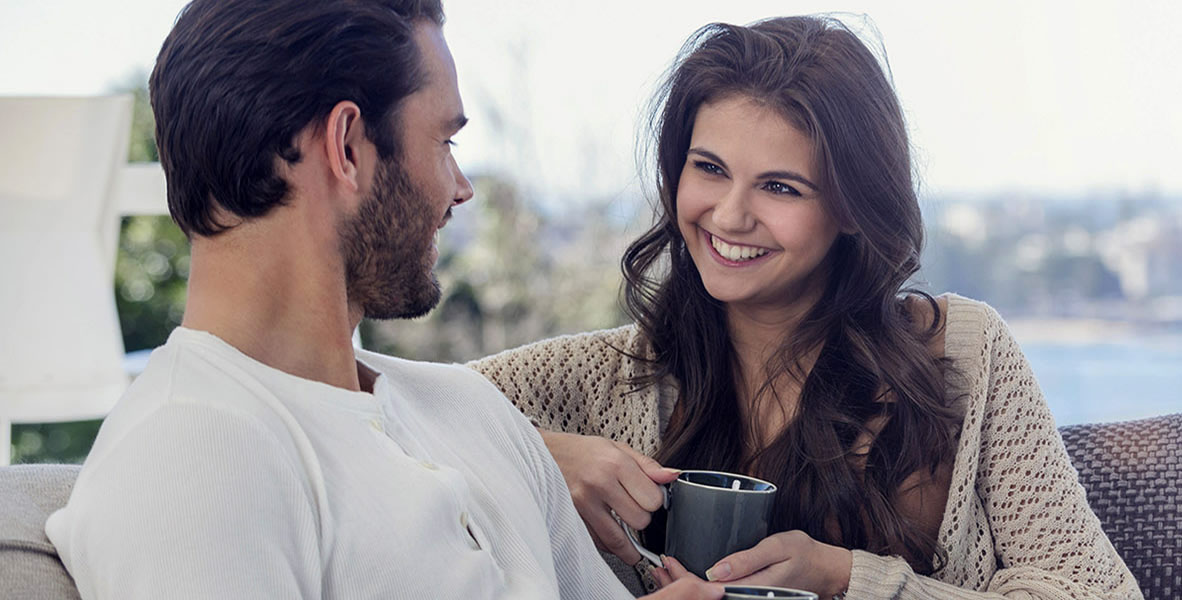 Couple drinking coffee on he sofa. They are sitting on a sofa. They are attractive, smiling and happy. There is a water view from the luxury house.